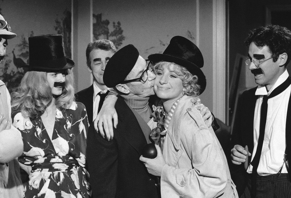 "Groucho Marx, has a kiss for Barbra Streisand as he visits the set of ""The Way We Were"" in Hollywood, Los Angeles on Nov. 2, 1972, where the actress and actor Brad Dillman, right, were doing a scene in which everybody dressed as a Marx Brother at a party. Director Sydney Pollack at left. (AP Photo/David F. Smith Ref #: PA.8940996  Date: 02/11/1972"