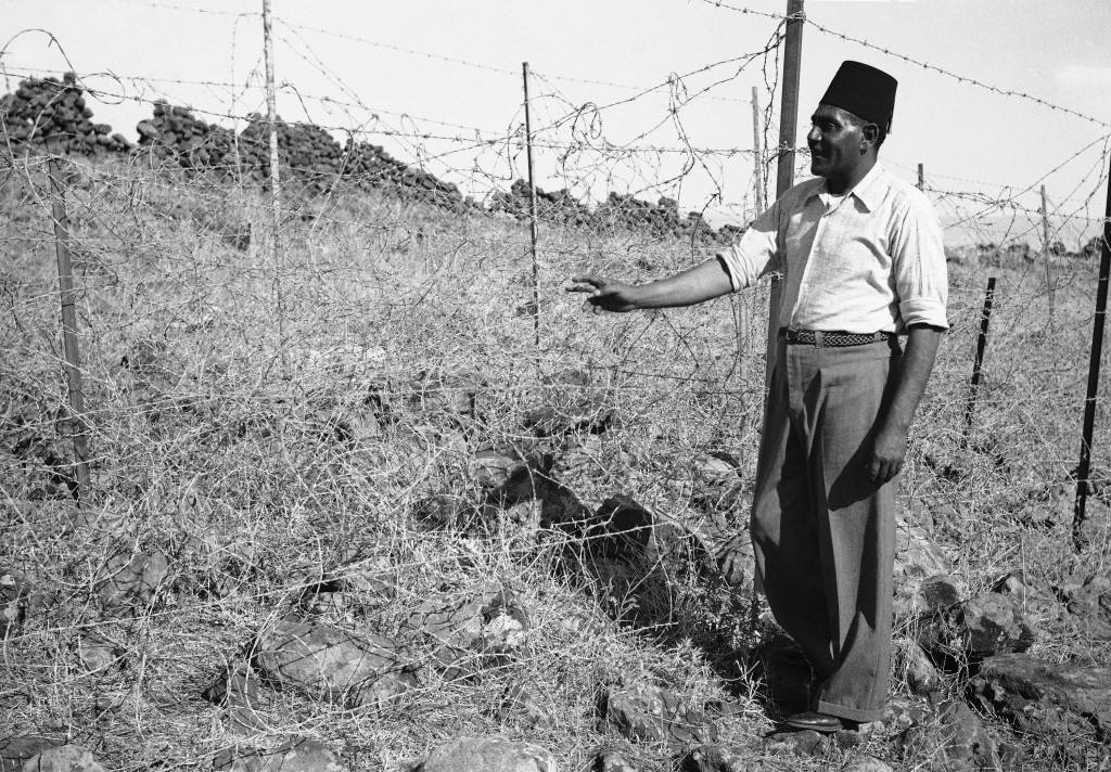 "An Arab stands beside a section of ""Tegart's Iron wall"" in Israel in 1938, erected by Sir Charles Tegart to keep marauding Arabs out of Palestine. The fence, three strains of barbed wire on angular iron supports. Stretches for 60 miles on the Syria-Lebanon borders and cost $ 500,000. (AP Photo/James Mills ) Ref #: PA.8988877 Date: 03/10/1938"