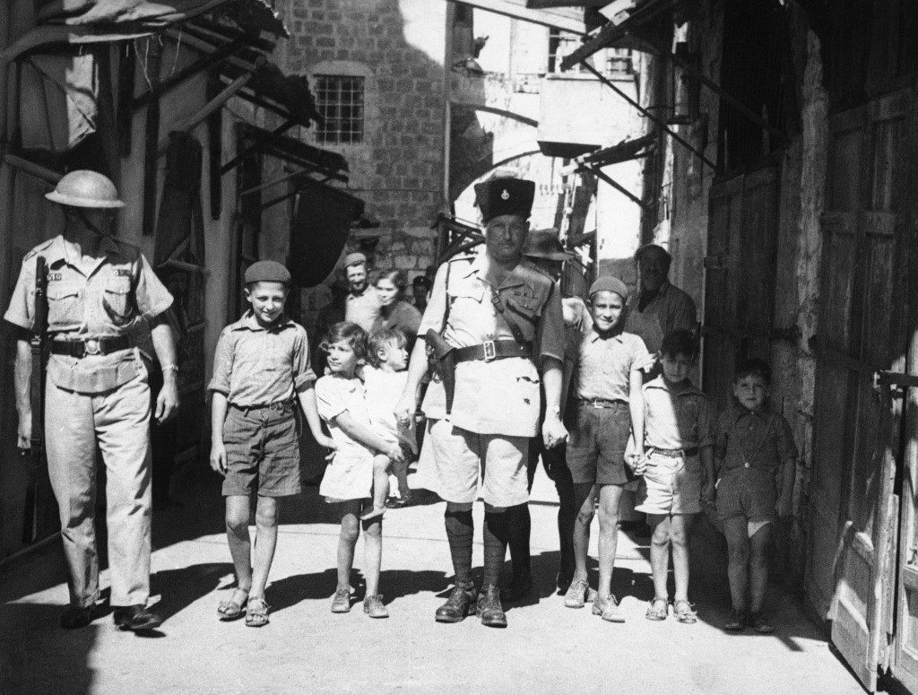 Since the British occupation of Jerusalem, Palestine, after the old city had been held for four days by Arabs, a measure of calm has descended on the district. Storm centre October 24—When this picture reached London by air after being was Jaffa, where there was sniping. British police captain leading Jewish kiddies to safety away from Arab snipers during the reoccupation of the old city of Jerusalem in Palestine, Israel on Oct. 24, 1938, by the British. (AP Photo/James Mills) Ref #: PA.8988895 Date: 24/10/1938