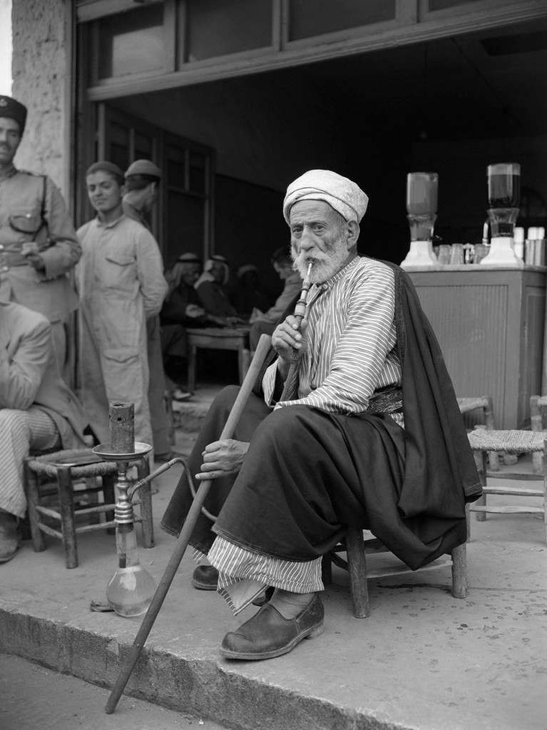 "A ""Hajj -"" an Arab who has been to Mecca and who is looked up by the ordinary Arab in Palestine. Here he is smoking his ""hubbly bubbly"" a tobacco smoke cooled by water in the jar in Jerusalem, July 17, 1947. (AP Photo/Pringle) Ref #: PA.8996271 Date: 17/07/1947"