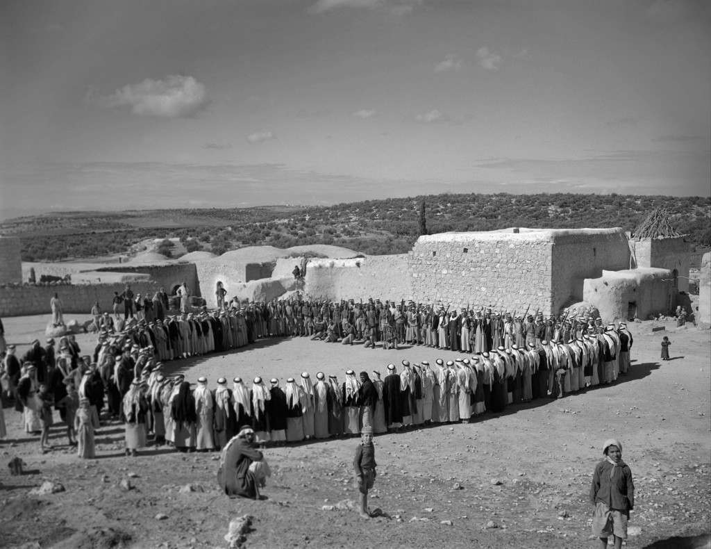 The scene at Arab hillside village on a Muslim Sabbath in Palestine, Jerusalem, Friday, March 31, 1948, when two families who had split the village into rival camps with a blood feud for the past two years set aside their differences, so that they might wage war against the Jews instead of each other. They're shown forming a rough circle with members of one family on the left, members of the other on the right, and Arab soldier volunteers in center background. Afterwards the male members of the two family factions advanced toward one another and shook hands. The feud, which began with the killing of a member of one family, was the first in Palestine thus formally set aside. The truce was solemnized by a feast. (AP Photo) Ref #: PA.8996275 Date: 31/03/1948