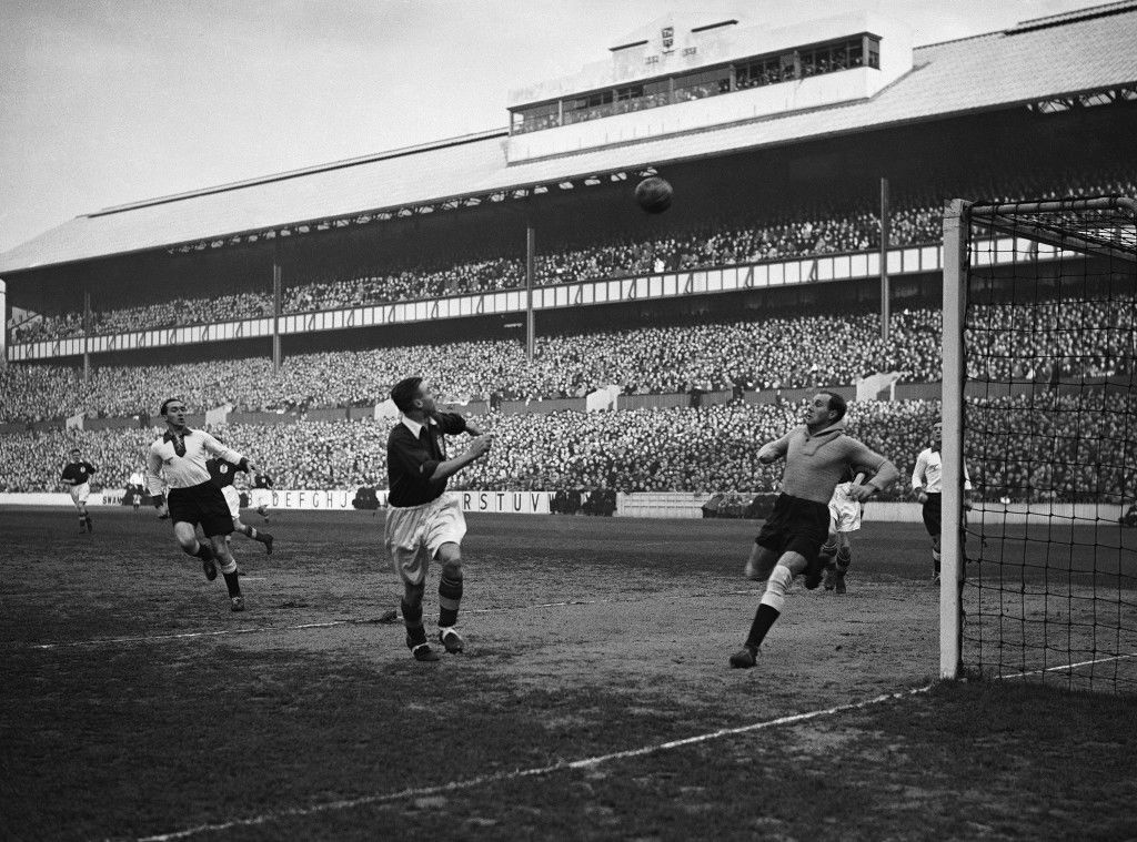 England playing Germany at football, at the Tottenham Hotspur football club ground, White Hart Lane, north London on Dec. 4, 1935. Hans Jakob, the German Goalkeeper, is seen running across the goalmouth to intercept a center during an attack by the English forwards. (AP Photo/Staff/Putnam)
