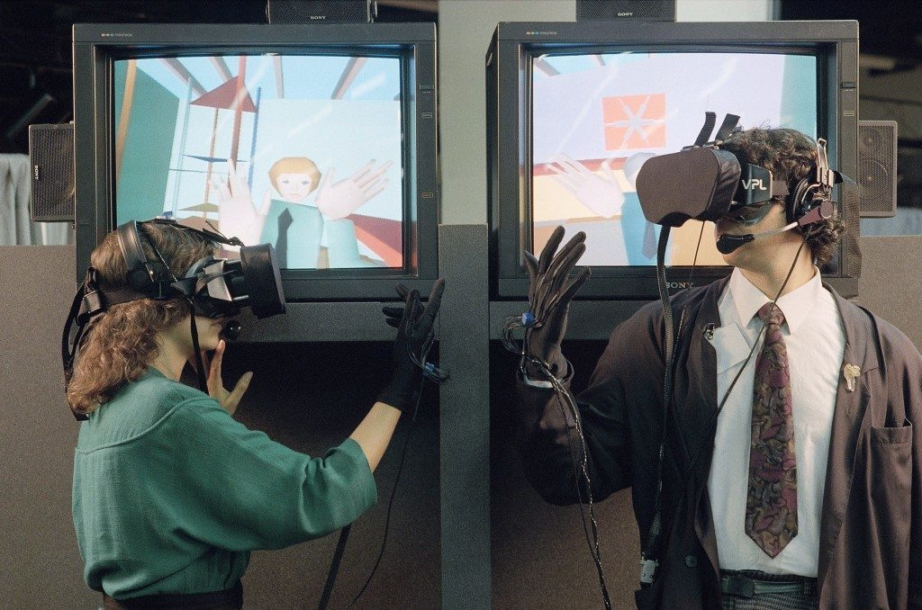 "Two people demonstrate the EyePhone system which uses special goggles and a ""DataGlove"" which allows them to see and move objects around in a computer created environment. The EyePhone, developed by VPL Research, is on display at the Texpo Telecommunications Show being held in San Francisco on June 7, 1989. (AP Photo/Jeff Reinking) Ref #: PA.9197076"