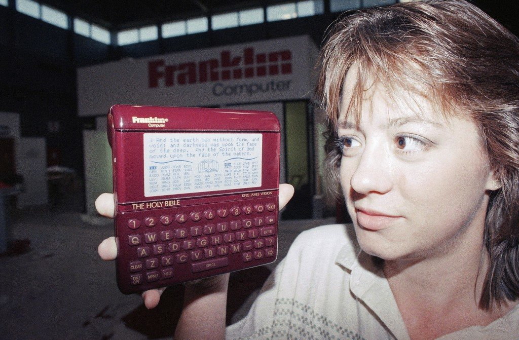 Patricia Ricalton of Franklin Computers in Mt. Holly, N.J., holds a Holy Bible computer during the Consumer Electronics Show in Chicago on June 2, 1989. The computer will be available in either the King James or revised standard versions and will include both the Old Testament and New Testament. (AP Photo/Mark Elias)