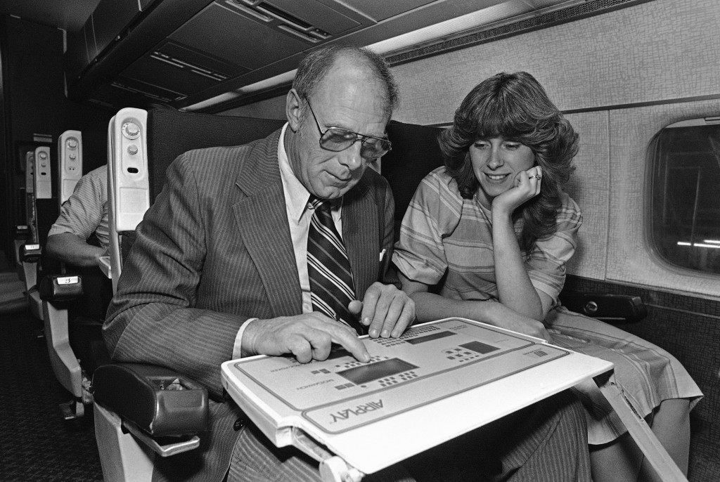 Untied Airlines employees try their luck at one of the computer games being installed in one of United's jets in their San Francisco maintenance facilities on June 8, 1984. The computers embedded in the tray table attached to the seat backs facing the passenger feature video backgammon, checkers, blackjack poker and soccer. Unlike the casinos, however, the on-board games are free and silent. (AP Photo/Mark Costantini)