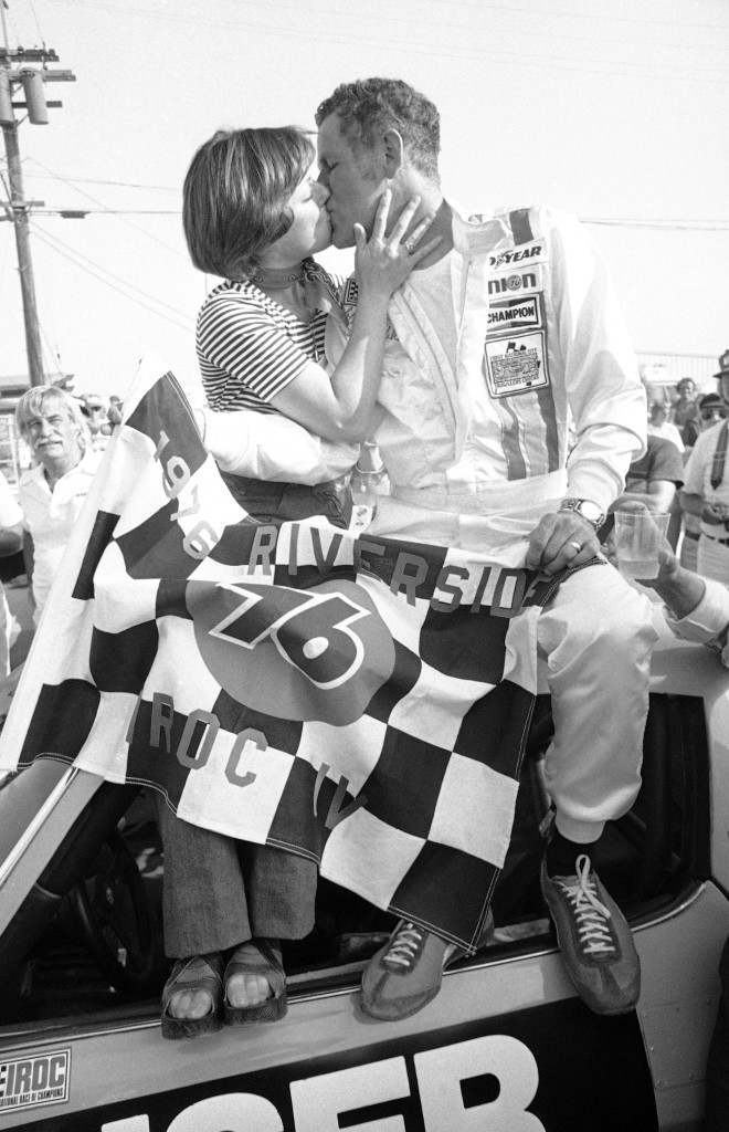 Bobby Unser receives a victory kiss from his wife, Marcia, after capturing the 76-mile International Race of Champions event at the Riverside, California Raceway, Oct. 16, 1976. Unser averaged 97.754 miles per hour to win the race, second in a four-race, $200,000 series. (AP Photo/George Brich) Ref #: PA.9200464  Date: 16/10/1976