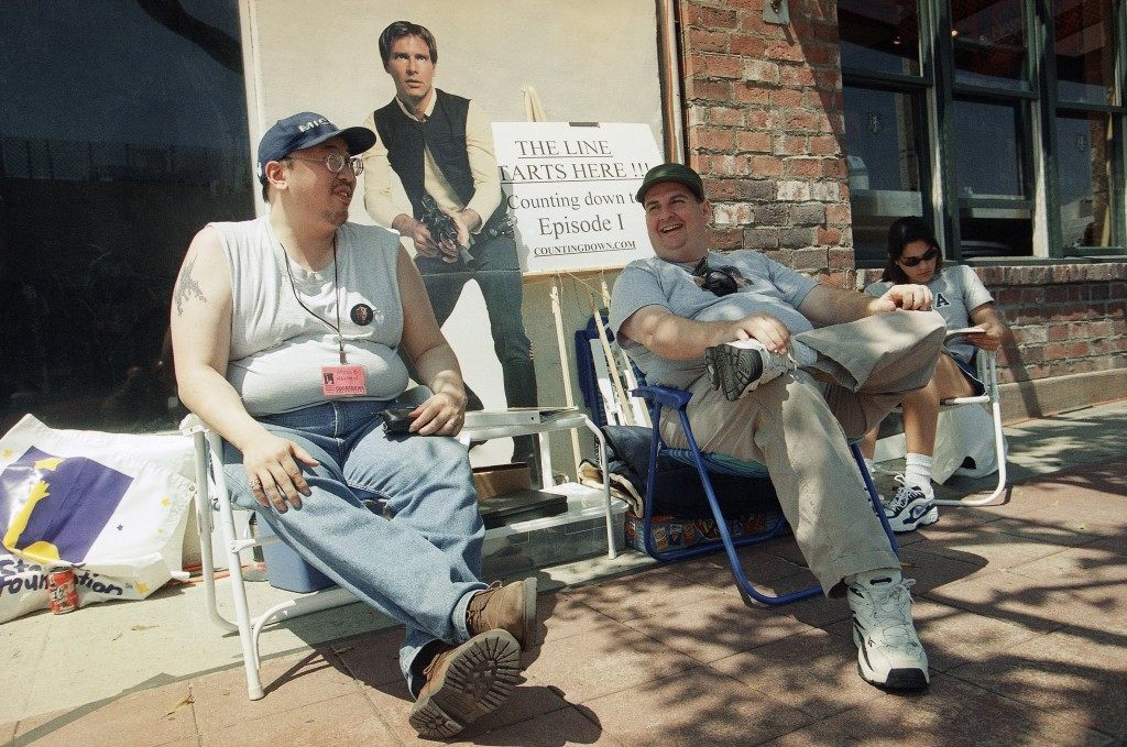 """Star Wars"" fans Apollo Nguyen, left, David Browne, center, and Monica Morero, all of Los Angeles wait outside the Mann Village Theater in Westwood, Los Angeles, Sunday, April 18, 1999 to be among the first ticket buyers for ""Star Wars: Episode 1- The Phantom Menace,"" Director George Lucas's next installment of the science fiction tale is set to hit theaters on May 19. Nguyen and Browne have been waiting outside the theater since April 9. (AP Photo/Chris Pizzello)"