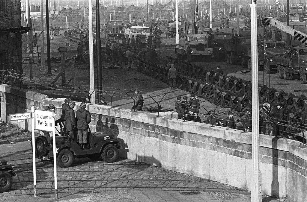Behind wall at border Stresemann and Kothener Strasse East German soldiers erecting tetrahedrons tank barriers made of streetcar tracks in Berlin Nov. 20, 1961. Background three American soldiers looking over the wall into West Berlin. (AP Photo/ Kreusch) Behind wall at border Stresemann and Kothener Strasse East German soldiers erecting tetrahedrons tank barriers made of streetcar tracks in Berlin Nov. 20, 1961. Background three American soldiers looking over the wall into West Berlin. (AP Photo/ Kreusch)