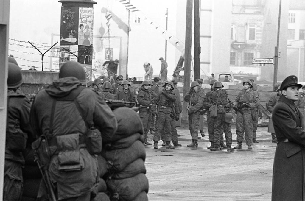 U.S. soldiers with automatic weapons stand behind sandbag barricade within few yards of East German soldiers assembled in front of workers adding to the wall at the Friedrich Strasse border crossing point in Berlin on Dec. 4, 1961. Communist authorities sent workers to several points along the wall on the East-West Berlin border, narrowing the gaps at the crossing points to restrict border passage. (AP Photo/Kreusch) PA-9300202