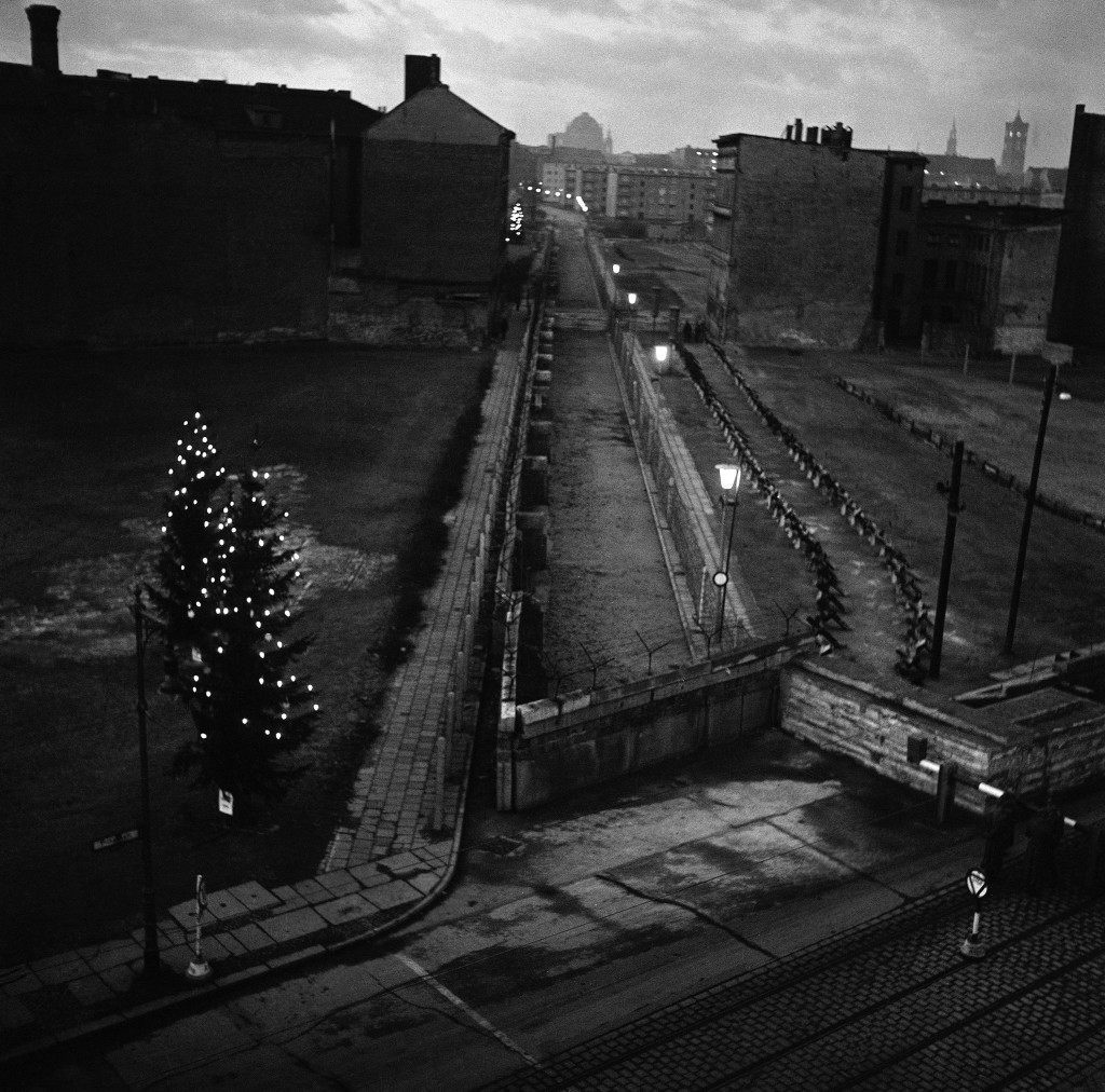 Lighted Christmas trees stand at the Heinrich Heine Strasse checkpoint in Berlin on Dec. 22, 1961. The East German wall, topped with barbed wire, runs up the center of the picture. Behind the wall, at right, in East Berlin, is a barbed wire fence, then a row of anti-tank obstacles. More than 800 Christmas trees have been set up by West Berliners along the wall. They are lighted at dusk everyday. (AP Photo) PA-9300616