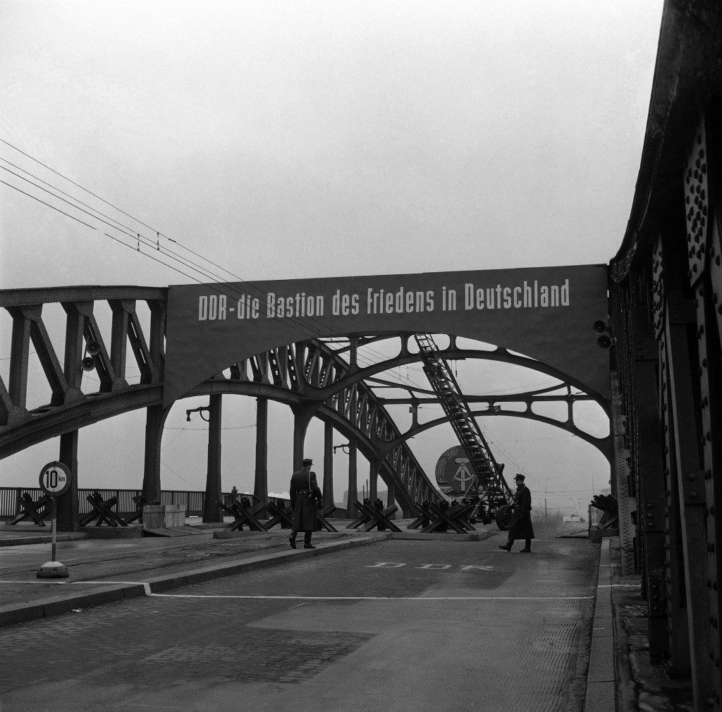 East Berlin people's police patrol the Bornholmer Bridge on the French-Soviet sector border Dec. 4, 1961 where a steel tank trip now spreads across part of the East German hammer and compass emblem appears in background as East Germany's communist Government worked to narrow the seven crossing points between East and West Berlin, by concrete walls and other methods, leaving small passages for traffic pass. (AP Photo/E.Worth) PA-9300620