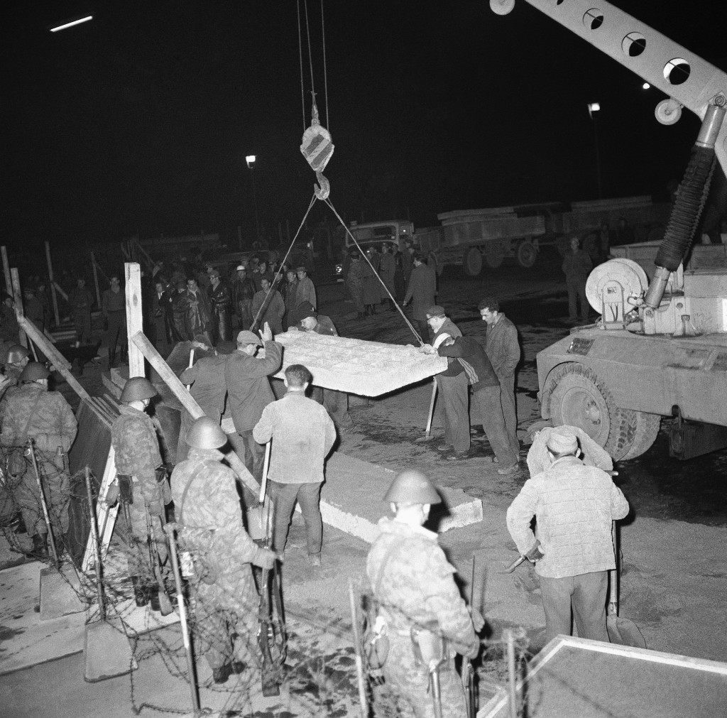 East German workmen guide crane lowering concrete block into position to make wall in front of Brandenburg Gate in East Berlin on Nov. 19, 1961. At left, armed East German soldiers watch the proceedings. Communists turned out hundreds of workmen all along wall dividing Berlin in what looked like a final effort to complete wall after three months of work. Workmen didn't arrive on scene until after nightfall and worked under floodlights. (AP Photo) PA-9300621