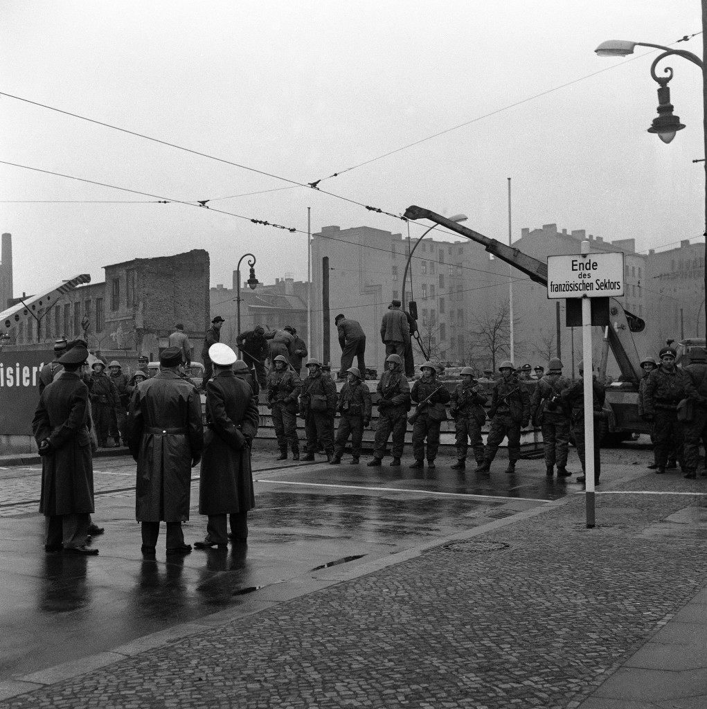 "Western observers watch at East Berlin workmen, behind a line of East German troops, push construction of the concrete wall, dividing the Russian-controlled sector of Berlin from the West. Scene is at Chausseestrasse in the French sector Dec. 7, 1961. Sign reads ""End of French Sector."" (AP Photo) PA-9300657"