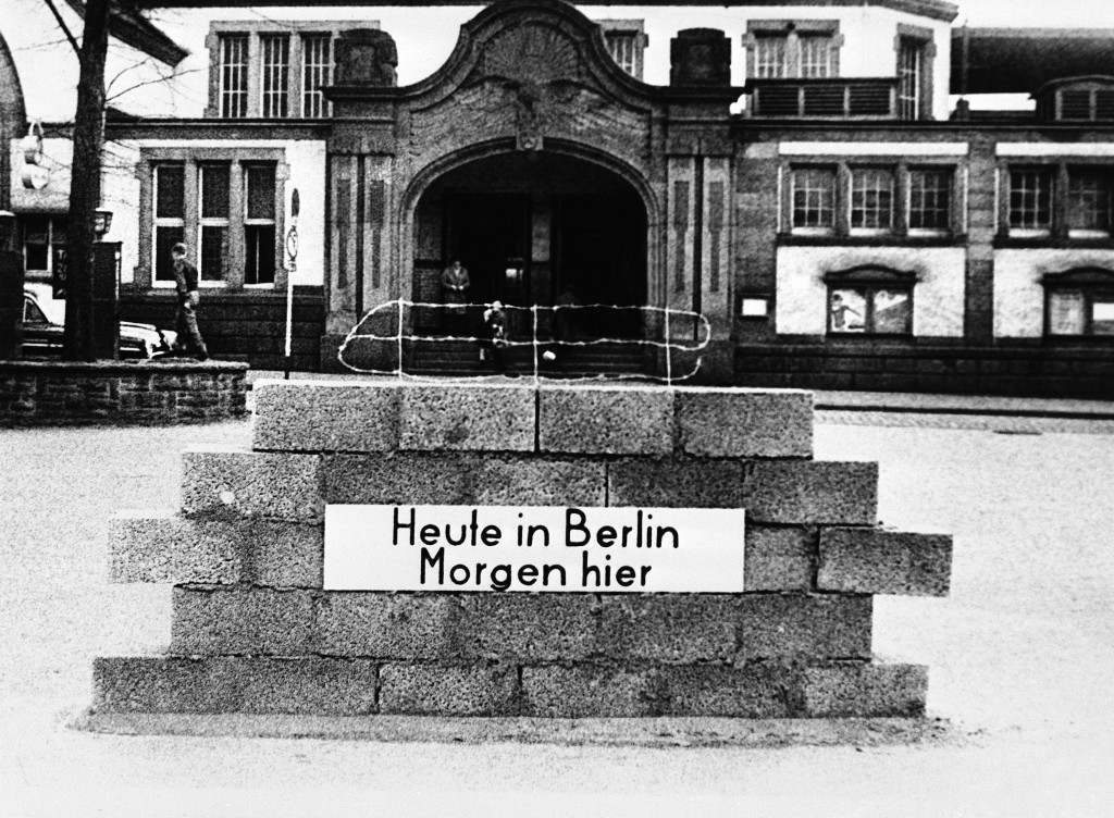 "Wall with barbed wire was set up by the West German refugee organization in front of the railway station in Schwerte, Germany on Dec. 13, 1961. It is to symbolize the situation in the divided city of Berlin. The sign at the wall reads ""Today in Berlin -- Tomorrow here"". (AP Photo) PA-9301495"