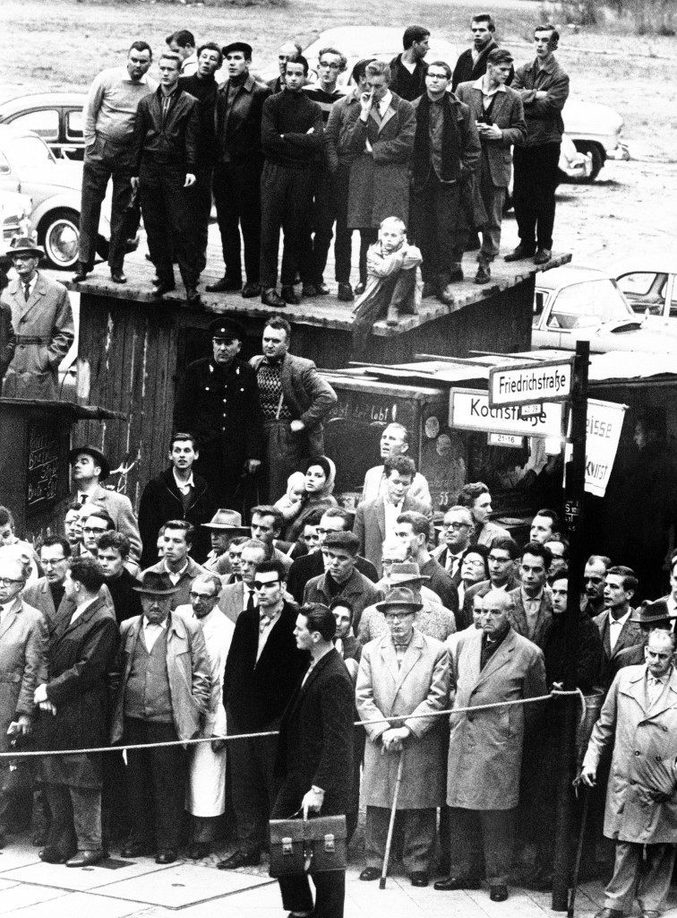 West Berliners watch the incidents at the U.S. Army checkpoint at the Friedrichstrasse where an American car and two sightseeing buses were barred entry by Communist East Berlin police, in Berlin on Oct. 25, 1961. (AP Photo) Ref #: PA.9301503 Date: 25/10/1961