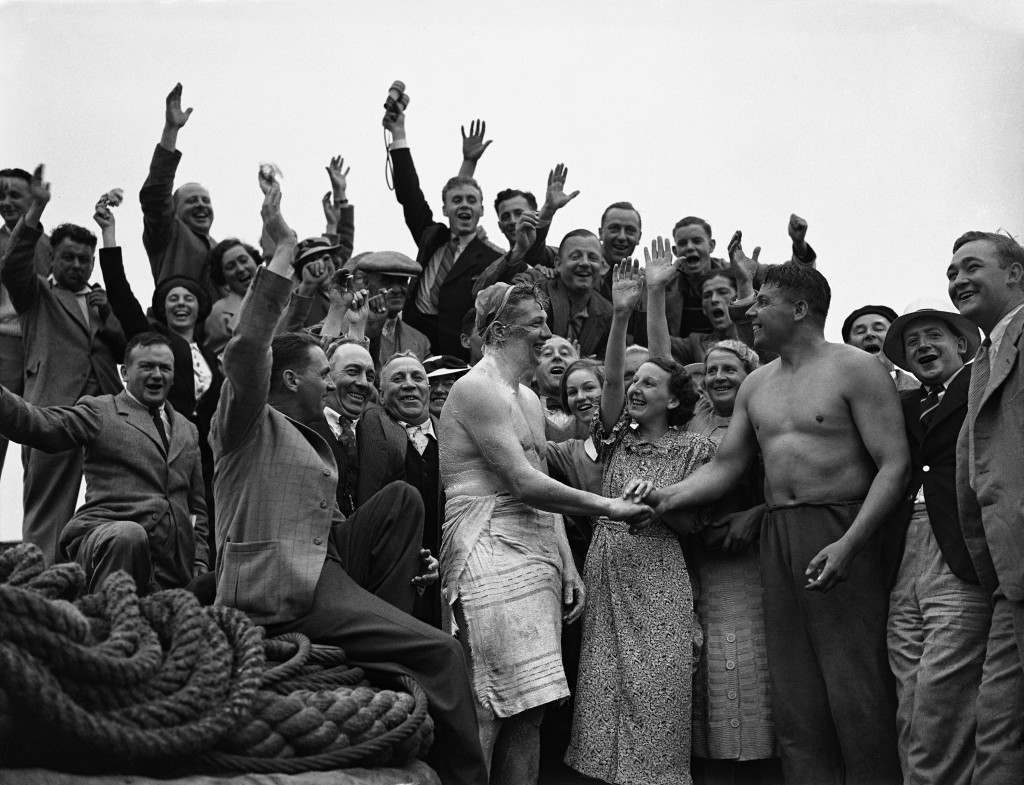 Tom Blower, left, a 23 year old factory worker who has swam the English Channel being congratulated by Edward Harry Temme on Aug. 4, 1937 in Dover, England. Temme is the first man ever to have swam The Channel in both directions. (AP Photo/Staff/Putnam) Ref #: PA.9305375  Date: 04/08/1937