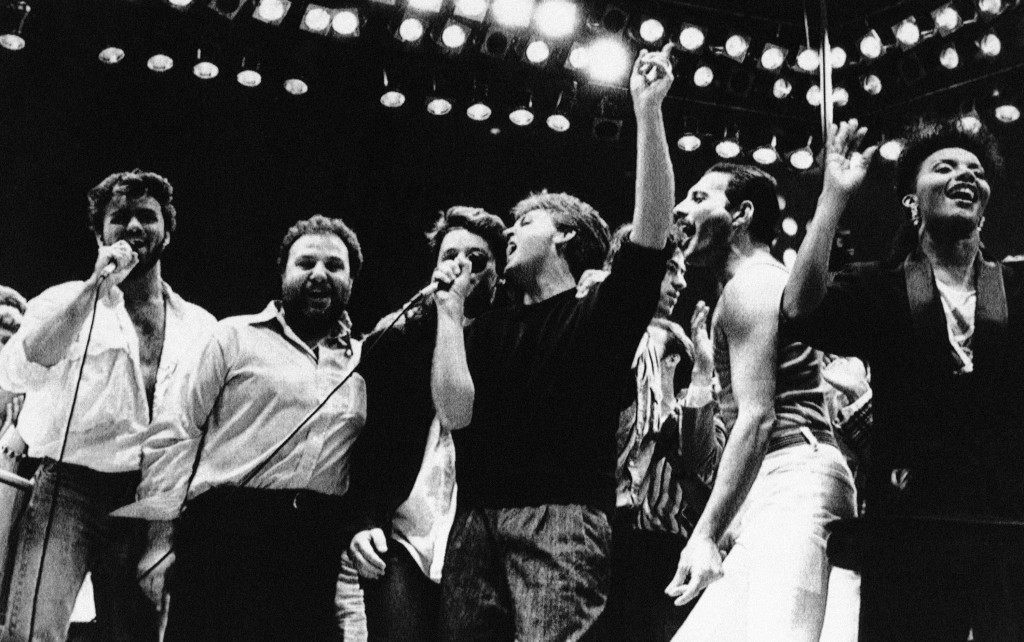 Paul McCartney,center with arm raised, joins in the finale of the London Live Aid Famine Relief Concert in London on July 13, 1985. Others, from left, are George Michael of Wham; Harvey Goldsmith, concert promoter; Bono of U2 (face obscured); McCartney; Bob Galdof, organizer; Freddie Mercury of Queen; and unidentified backing singer. (AP Photo/Joe Schaber)