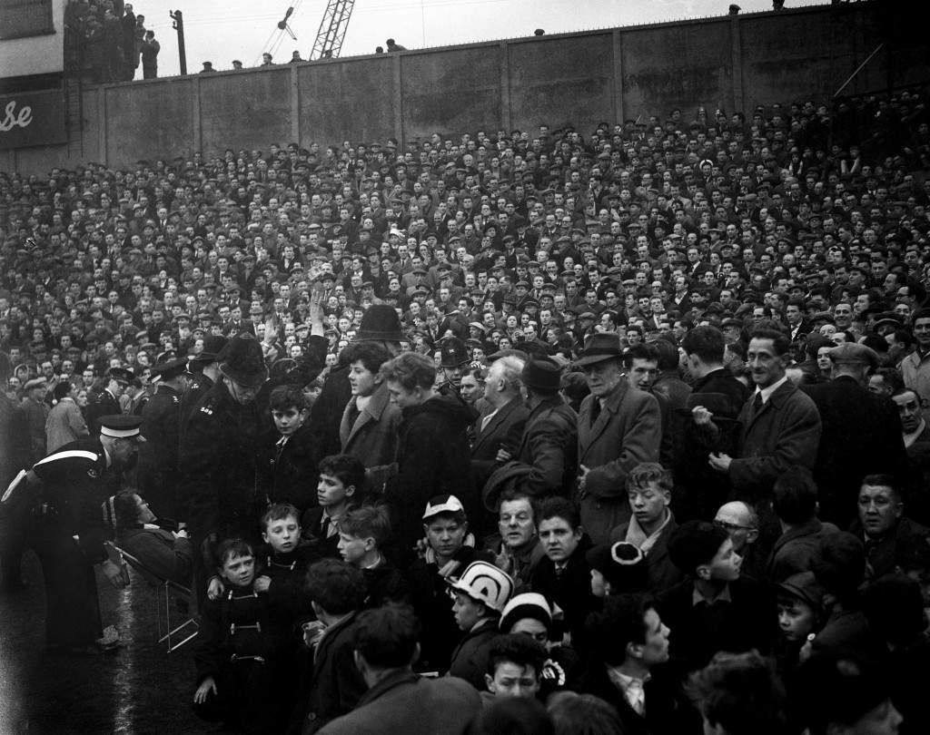 Football - Millwall V Newcastle United - London Members of the police force attempt to control the seething crowd as they swarm over the fences onto the edge of the pitch. Ref #: PA.9336905  Date: 26/01/1957