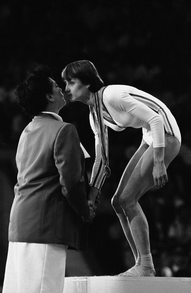 East German official Ellen Burger gives kiss to Romanian gymnast Nadia Comaneci during medal presentation for the women's gymnastics individual apparatus event at Moscow Olympics on July 25, 1980. Nadia won the gold for her performance on the balance beam. She won a second gold, which she shared with Soviet Nelli Kim, for floor exercise. (AP Photo) Ref #: PA.9353144  Date: 25/07/1980