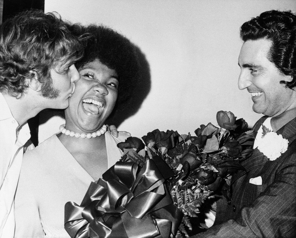 "Yolanda King, center, 15-year-old daughter of slain civil rights leader Dr. Martin Luther King, receives a kiss from her leading man Gregory Patin, left, and roses from her director Walter Roberts, right, in Atlanta, June 20, 1971. Miss King made her stage debut in the Atlanta Actor's Workshop production of ""The Owl and the Pussy Cat"". She has the female lead in the play. (AP Photo) Ref #: PA.9367336  Date: 20/06/1971"