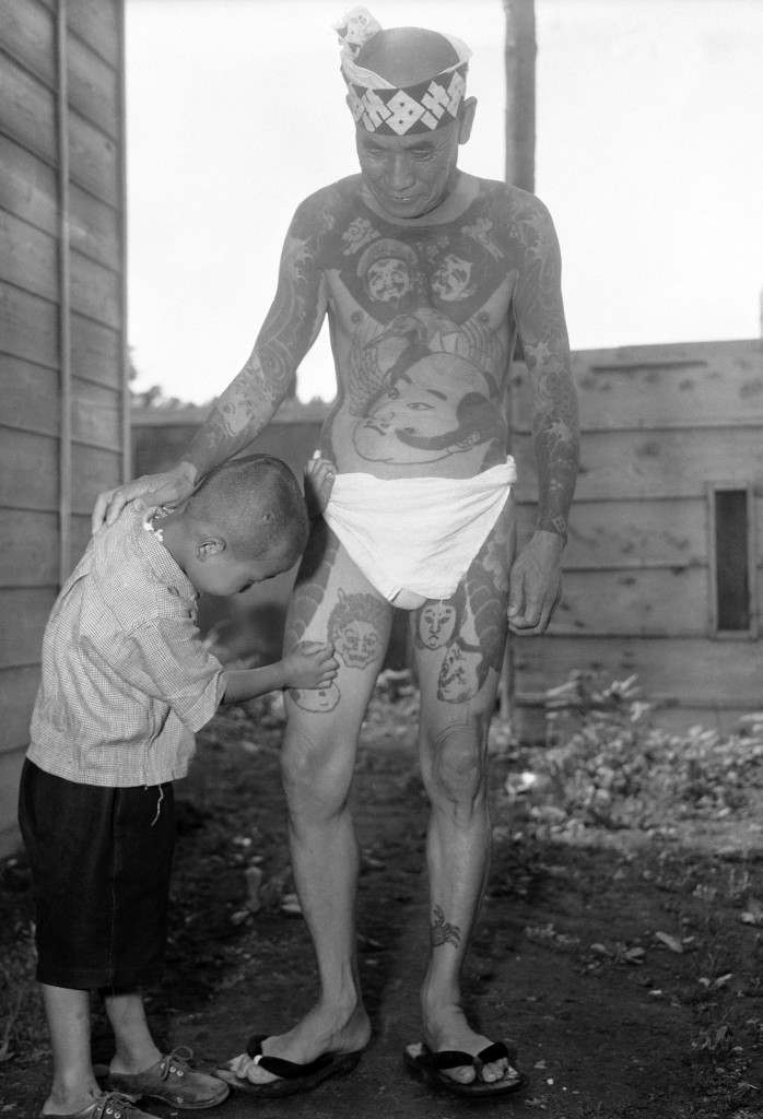 "At the ""Hard Skin Club"" convention of tattooed men and women in Tokyo, a little boy examines a design on his father's leg in Tokyo, Sept, 2, 1948. Eighty club members – including three women met for their first convention in nine years in one of the city's small parks. (AP Photo/Charles Gorry) Ref #: PA.9431346"