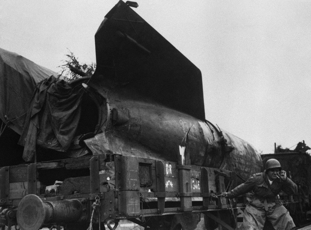 A train carrying nine V2 bombs has been captured intact by the American First Army. The rockets were found to be intact but unassembled. An American soldier takes a great risk as he strikes a match on one of the trailers, to light his cigarette near Bromskirchen, Germany, on April 7, 1945. (AP Photo) Ref #: PA.9461508  Date: 07/04/1945