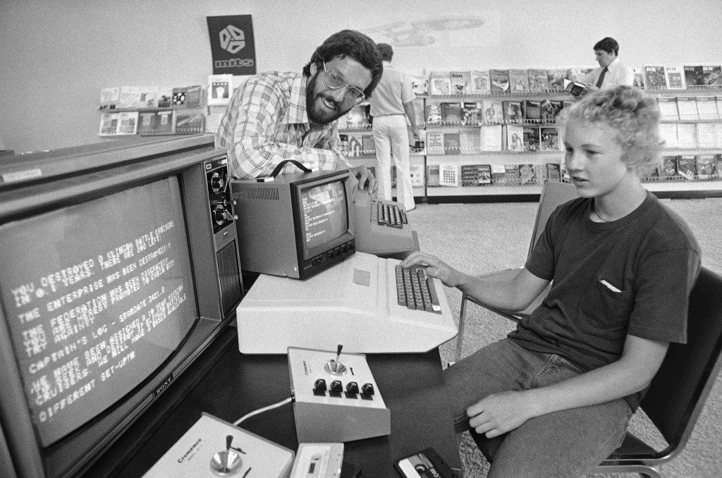 "Richard Conner, 15, plays a game of ""Star Trek"" on a small, relatively cheap ""home"" computer at the Computer Store which is owned by Dick Heiser, left, in Los Angeles on Sept. 22, 1977. The so-called microcomputers are used for everything from playing games to doing your income tax yourself. (AP Photo/George Brich)"