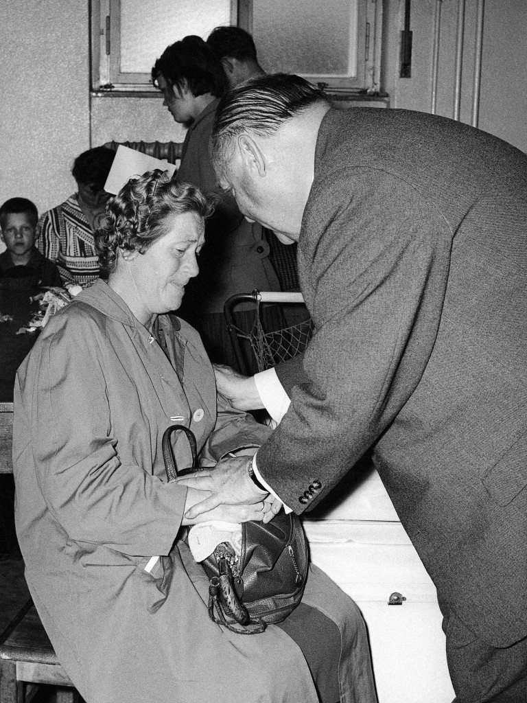 Tears of happiness and relief ran over the face of this woman when she was ready with the reception formalities after she fled with about 1,000 other people from communist East Germany to West Berlin. On the same day the minister for All German Affairs, Ernst Lemmer, was looking after the refugees and paid a visit to the refugee camp in Berlin-Marienfelde. Here Lemmer is talking to the woman and says some comfort words and holds her hands in Berlin, Germany on July 13, 1961. (AP Photo/Werner Kreusch) Ref #: PA.9730823