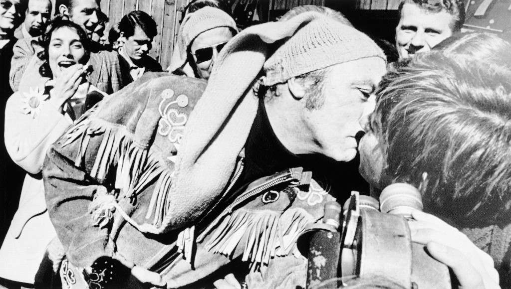 Canada's Prime Minister Pierre Trudeau (foreground) leans over to kiss an unidentified young lady to the seeming surprise of his recent bride Margaret, left, in St. Joseph Du Lac, Quebec March 27, 1971. Prime Minister and Mrs. Trudeau spent Saturday at maple free farm here near Montreal at a sugaring out party for Mr. Trudeau's constituents of Mount-Royal. (AP Photo/PBR) Ref #: PA.9830566  Date: 27/03/1971