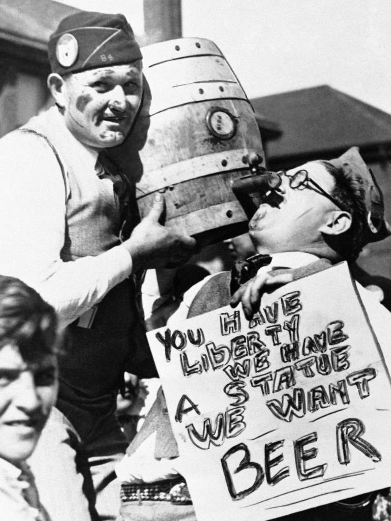 """A prohibition-thirsty American Legionnaire goes into action in Windsor, Canada August 17, 1954, where the beer flowed freely, during the 1931 Legion convention across the river and the border in Detroit, Mich. His sign reads: """"You have liberty - we have a state - we want Beer"""". Legion officials have decreed a """"safe and sane"""" convention this year, in Washington, D.C. (AP Photo) Ref #: PA.9914531  Date: 01/01/1931"""