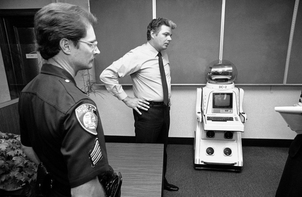 Sgt. Tom Van Ansdell of the Beverly Hills, Calif., police department displays a 4-foot robot at police station in Beverly Hills on August 18, 1982. The robot, complete with color television screen and camera, micro computer and two-day communications, was taken into police custody after it was found clanking through Beverly Hills during Tuesday rush hour. Police took the robot into custody when the person, as yet unidentified, operating it by remote control, refused to identify himself to police. (AP Photo/Lennox McLendon)