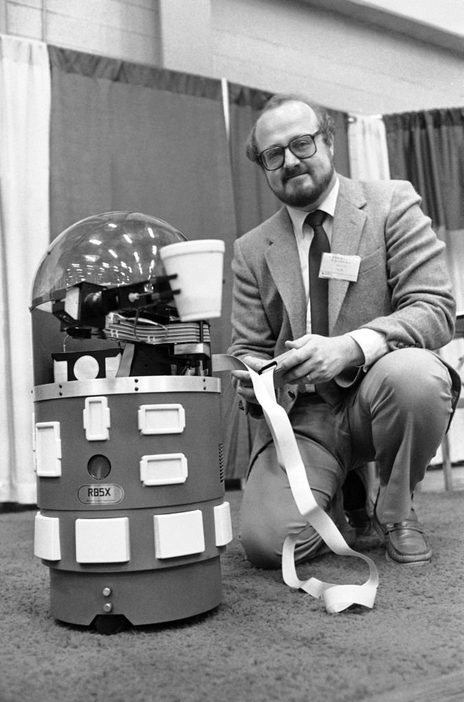 Richard J. Nelson of the RB Robot Company sends a model 5X through its paces at the annual Atlanta Computer Show in Atlanta on Dec. 8, 1983 by having it offer a cup of coffee to viewers. (AP Photo/Joe Holloway Jr.)