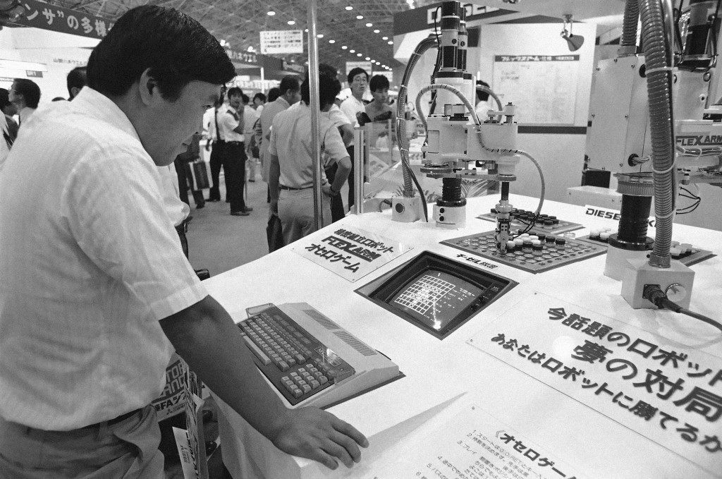 This visitor to a Tokyo robotics show plays the oriental board game of 'Go with a computer - robot combination that figures out opposing moves, then actually moves the pieces in Tokyo on Thursday, Sept. 8, 1983. Japanese and foreign firms which specialize in the rapidly growing field exhibited their products at the show. (AP Photo/Katsumi Kasahara)