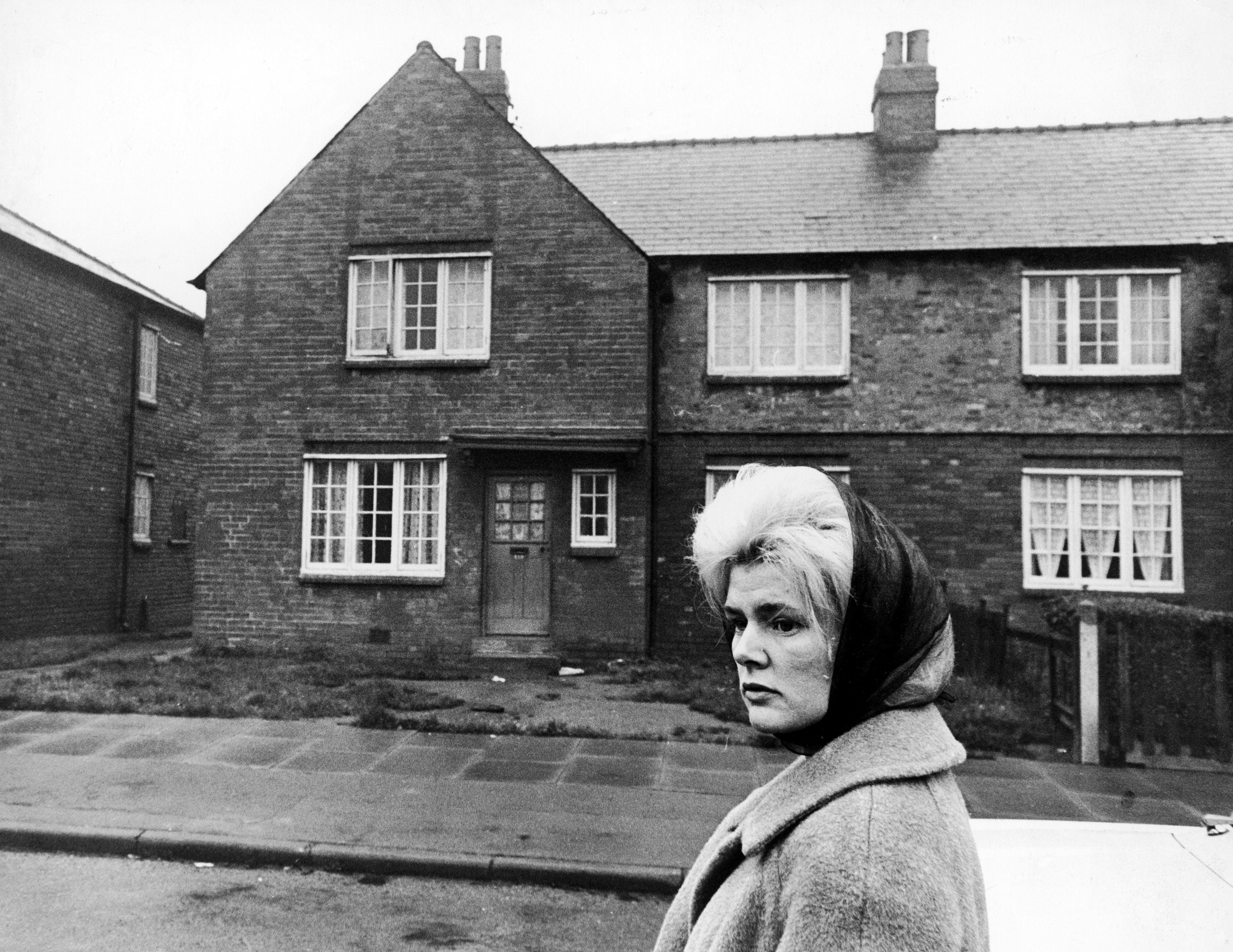 Original caption: The first big winner on the football pools, Viv Nicholson, returns to the street where she lived before striking it rich, her 38 shilling a week council house behind her.