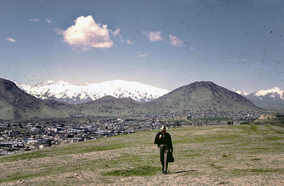 """Dr. Bill Podlich on a hillside in Kabul. """"My dad was a professor of Elementary Education, specializing in teaching Social Studies, at Arizona State University in Tempe, Arizona from 1949 until he retired in 1981. He had always said that since he had served in WWII (he trained soldiers against chemical warfare), he wanted to serve in the cause of peace. In 1967, he was hired by UNESCO as an Expert on Principles of Education, for a two-year stint in Kabul, Afghanistan at the Higher TeachersÕ College. Throughout his adult life, because he was interested in social studies, whenever he traveled around (in Arizona, to Mexico and other places), he continued to take pictures. In Afghanistan he took half-frame color slides (on Kodachrome), and I believe he used a small Olympus camera."""" - Peg Podlich."""
