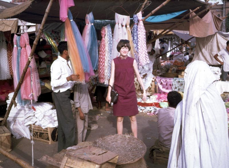 """Jan Podlich on a shopping trip in Istalif. Jan in a short, sleeveless dress and the woman to the right in a chadri (burka). """"We arrived in Kabul one sunshiny morning in June... My dad met us and was able to whisk us through the customs. We proceeded into Kabul in a UN 'kombi' (kind of an old school SUV). I was tired, but I can remember being amazed at the sight of colorful (dark blue, green and maroon) ghosts that were wafting along the side of the road. My dad explained there were women underneath those chadris, and that some women had to wear them out in public. We never called the garments burkas... Depending on the country, women practicing purdah (Islamic custom requiring women to cover up) wear different styles of coverings, which have different names."""" - Peg Podlich"""