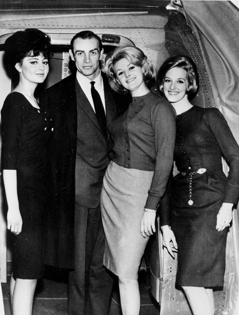"Actor Sean Connery is flanked by ""Bond Girls,"" while on the set of the latest James Bond 007 thriller ""Goldfinger,"" at Pinewood Studios, near Iver Heath. Standing immediately next to him on the right is Shirley Easton, who plays the character Jill Masterson, others are unidentified."