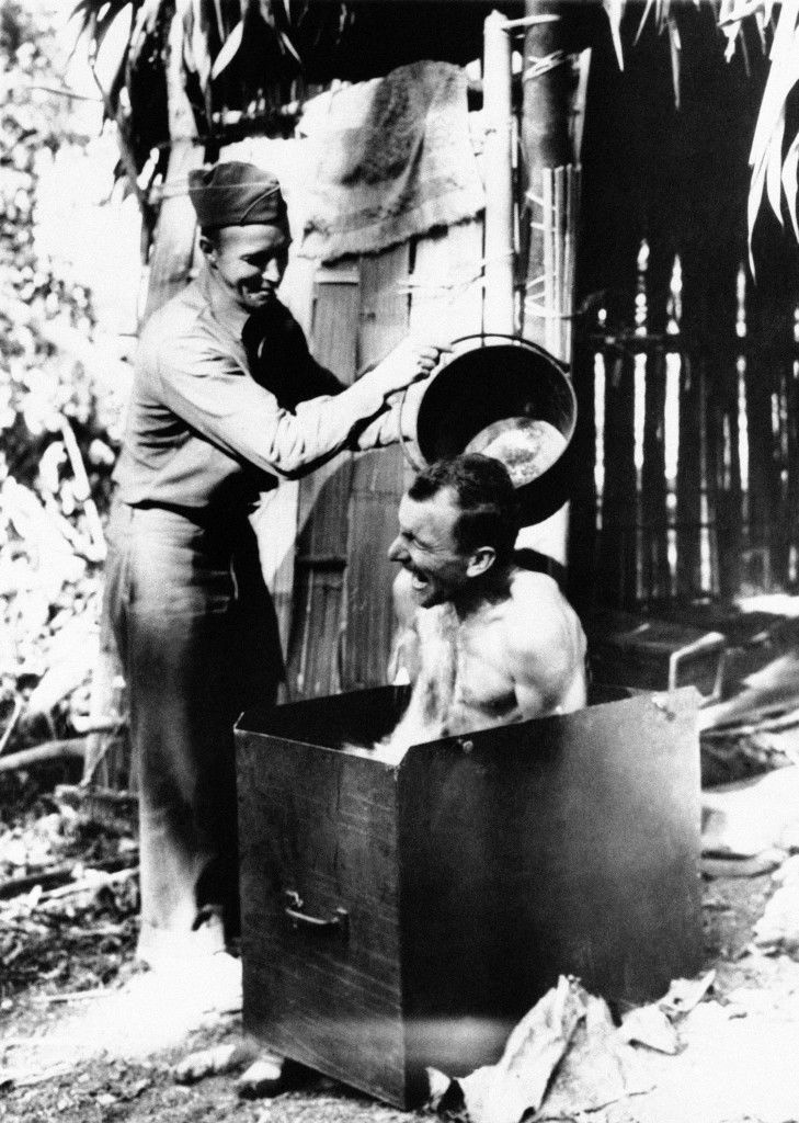 """Outside his thatched bamboo """"cottage,"""" Cpl. George W. Powell, of St. Petersburg, Fla., enjoys a bath as Sgt. Arne A. Metsa, of Chassell, Mich., pours the water in Naga Hills, India on Feb. 21, 1943. Tub was made from the cover of a piece of equipment. Both are with U.S. troops in the area. (AP Photo)"""