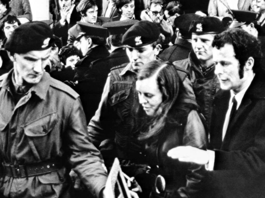 Bernadette Devlin, firebrand Catholic civil rights leader and Member of Parliament for Mid-Ulster, surrounded by British troops, leaves court at Londonderry, Northern Ireland, on Dec. 22, 1969, after receiving six months jail sentence on charges of inciting people to riotous behavior. (AP Photo) Ref #: PA.10346486  Date: 22/12/1969
