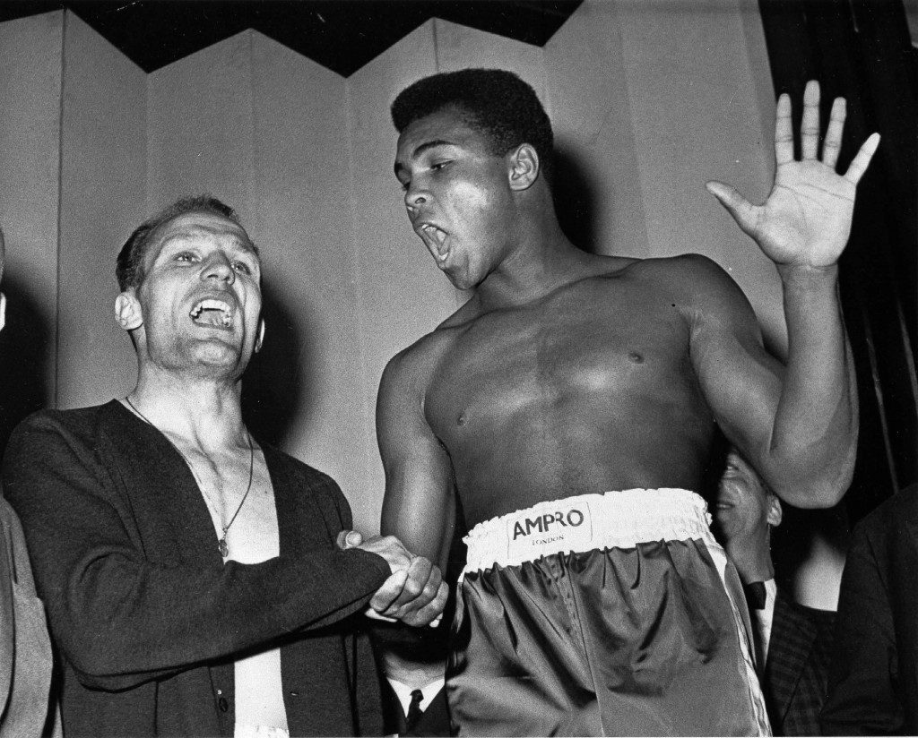 A June 18, 1963 photo from files showing world famous boxer Muhammad Ali (or Cassius Clay as he was then known), right, and British heavyweight champion Henry Cooper as they seem to be trying to out shout each other at weigh-in in London for their heavyweight fight the same evening. Ali holds up five fingers, the number of rounds he modestly predicts he'll knockout Cooper