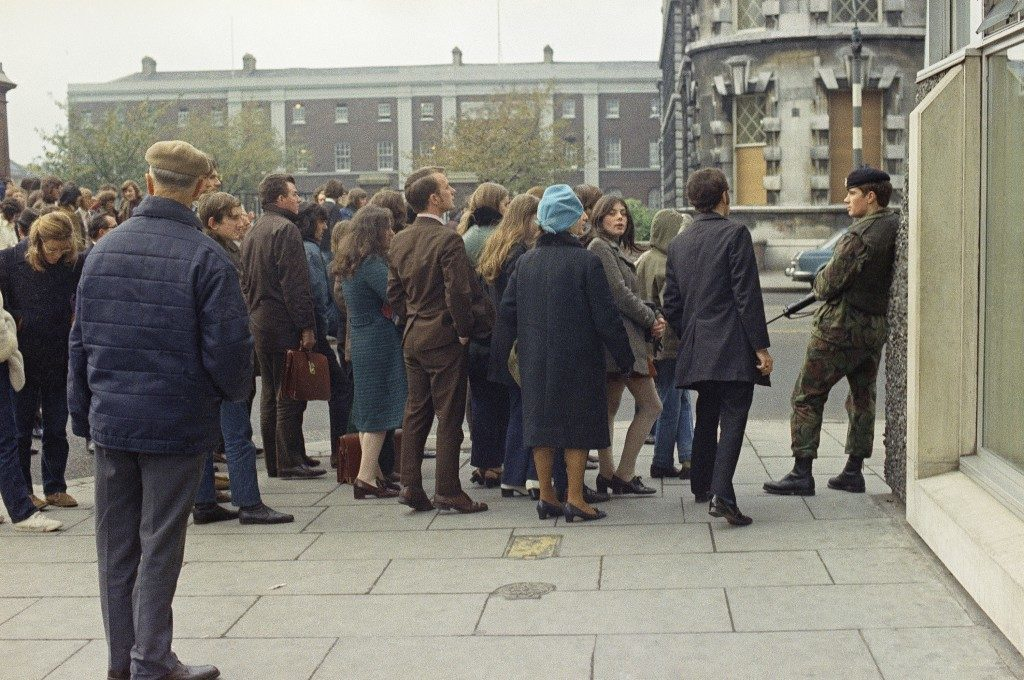 A British soldier stands guard as bystanders wait to get a view of operations by the army bomb disposal squad in Northern Ireland on Nov. 11, 1971 after an explosive device had been planted near the city centre. (AP Photo) Ref #: PA.10765953