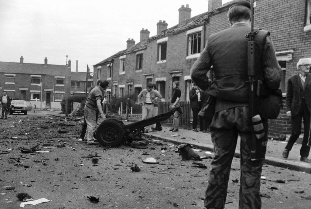 A British soldier, and residents of Alliance Parade, Belfast, Northern Ireland, examine the remains of a car bomb which severely damaged their homes in Belfast on July 14, 1972. (AP Photo/Peter Kemp) Ref #: PA.10778610