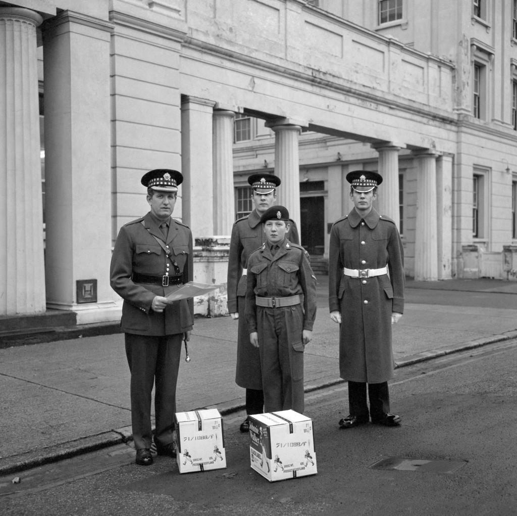 To help the 1st Battalion Scots Guards, at present serving in Northern Ireland, celebrate Hogmanay in the traditional manner, the North-East London Army Cadet Force has presented them with two cases of 'Hard Rations', known to civilians as Scotch whisky. Army Cadet Force Lance-Corporal Anthony Jackson (in beret) presented the cases to Major J R Arthur, Regimental Adjutant, Scots Guards, at Wellington Barracks, London. Ref #: PA.10981757 Date: 22/12/1971
