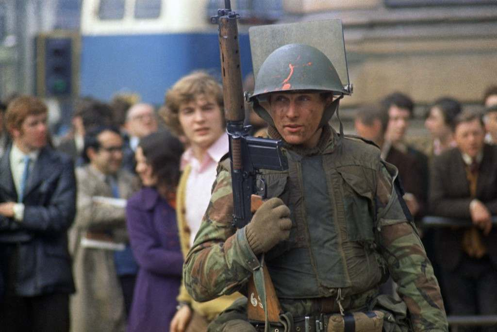 A British soldier stands guard in a Londonderry Street on following a bomb outrage near the city centre in April 1972. (AP Photo) Ref #: PA.10990759