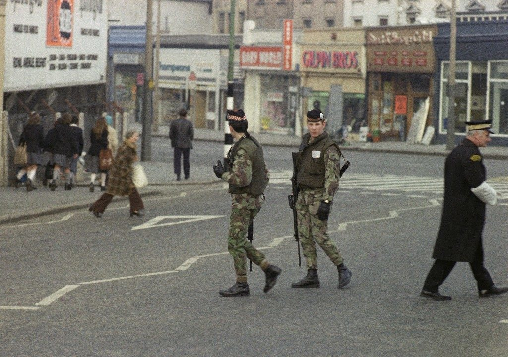 Shoppers in Belfast, Northern Ireland go about their business with almost total indifference to a British Army street patrol in 1976. (AP Photo) Ref #: PA.11032241