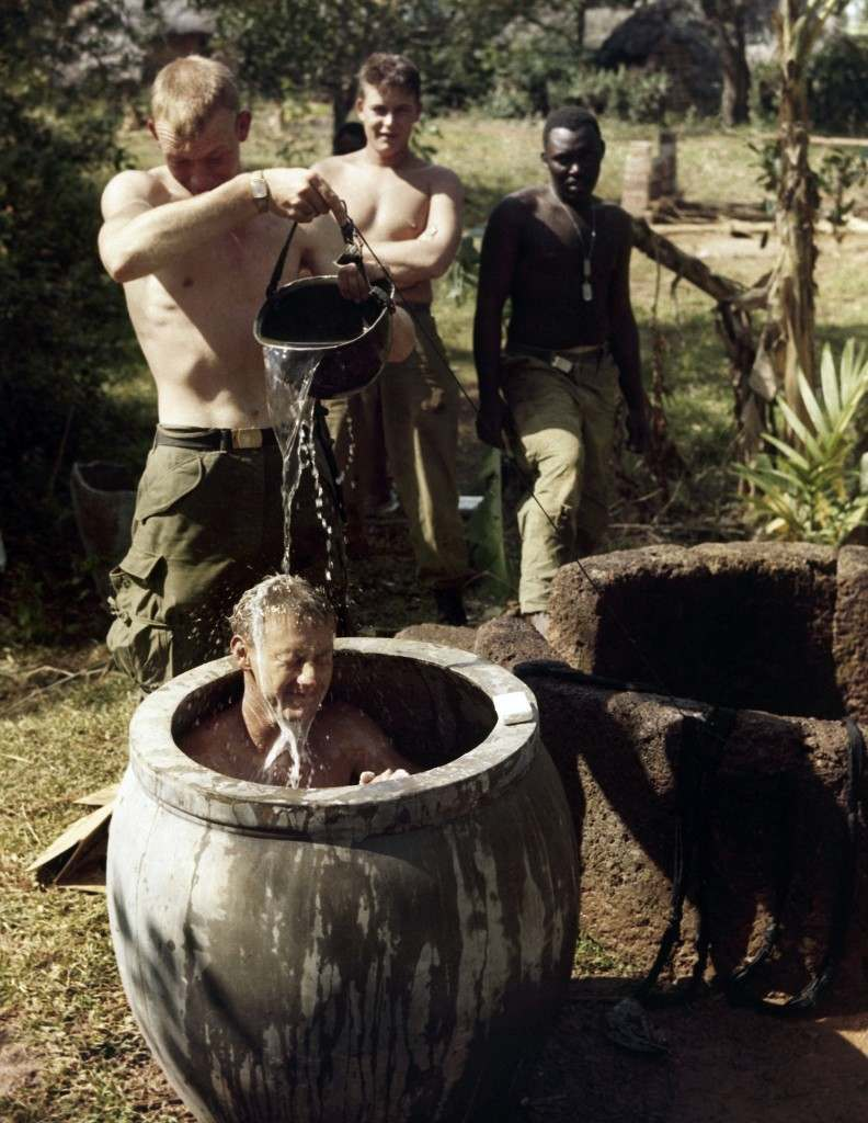 Sp4 Mack A. Hassier of Crab Orchard, Tenn. pours water from a helmet over Pfc. Lee A. Bilbrey of Pleasant Hills, Tenn. taking his first bath in 10 days in a Vietnamese crock on March 7, 1966 after being pulled back from front line for a rest. Unit remained on 30 minute alert. (AP Photo)