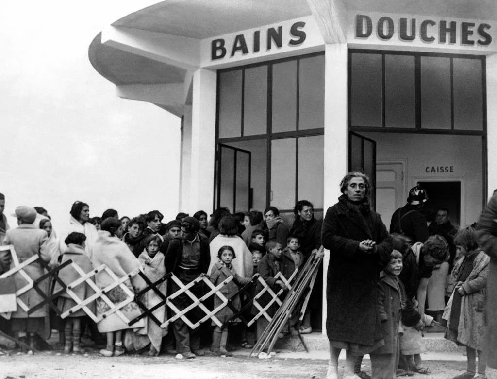 While General Franco's forces continue their advance northwards from Barcelona, and endless and pitiful stream of refugees, men, women, and children throng all the roads leading to the French Frontier. Many weary refugees were taken to the French town of Boulou, 11 kilometers from the Frontier, where they were able to rest and were given welcome free baths after their long trek. Some of the refugees lining up for the delights of a refreshing bath after their weary trek from Spain to the town of Boulou, France, on Jan. 29, 1939. (AP Photo)