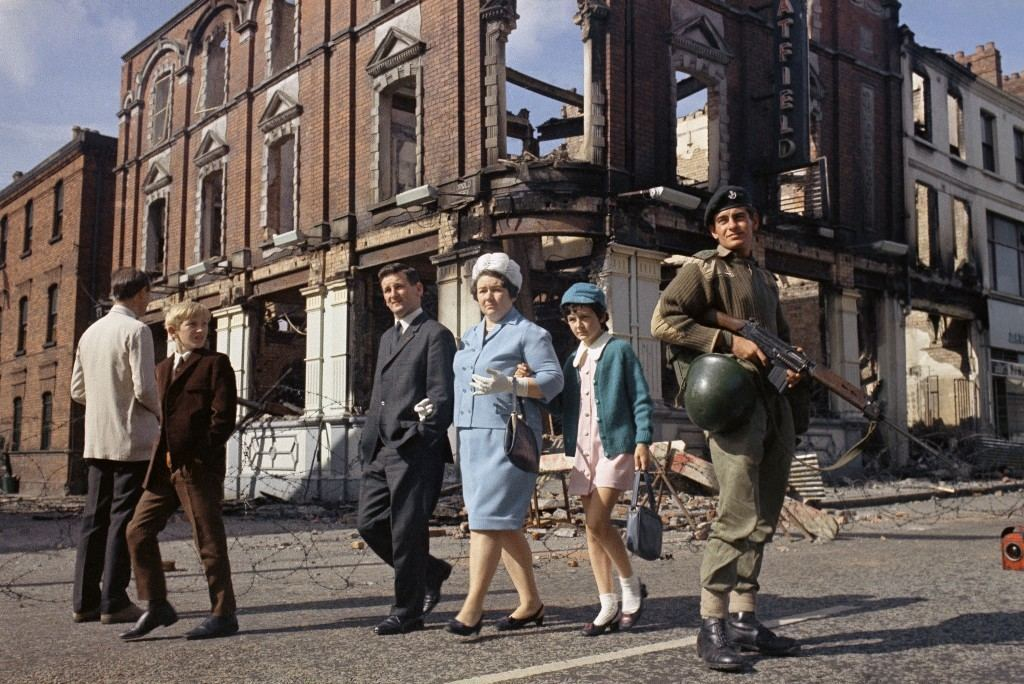 Local people walk past British troops on guard in the streets after violence in Northern Ireland in August 1969. (AP Photo/Peter Kemp) Ref #: PA.11197900