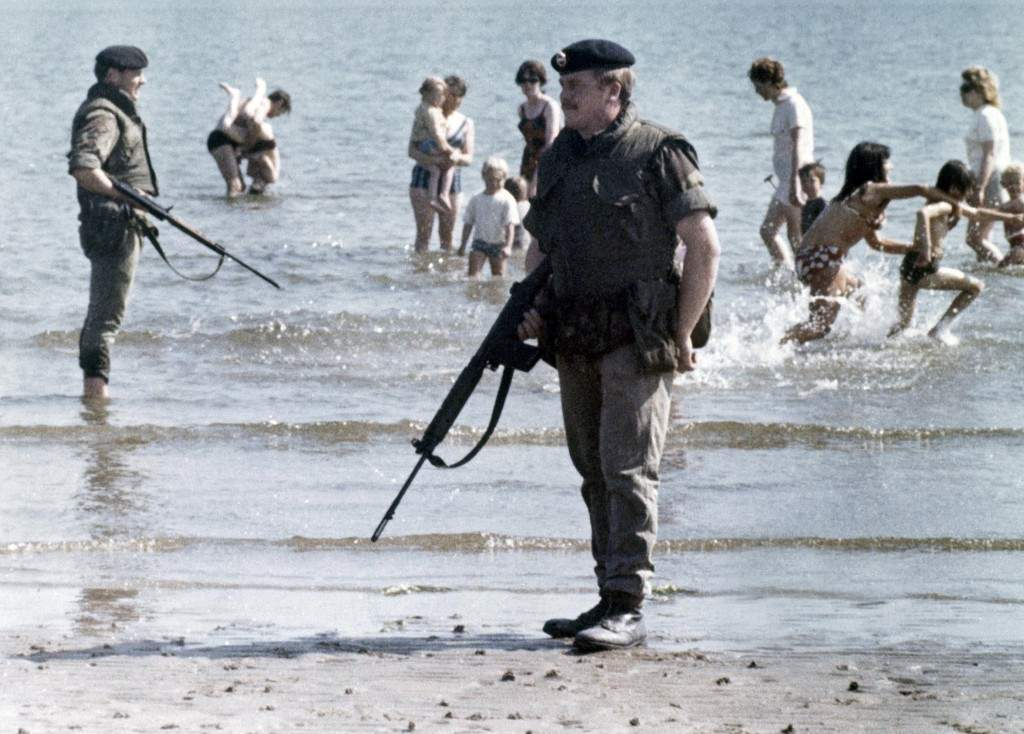 British troops stand guard on a beach near Belfast, Northern Ireland's capital in July 1972, as local families bath in the sea. (AP Photo/Peter Kemp) Ref #: PA.11384803
