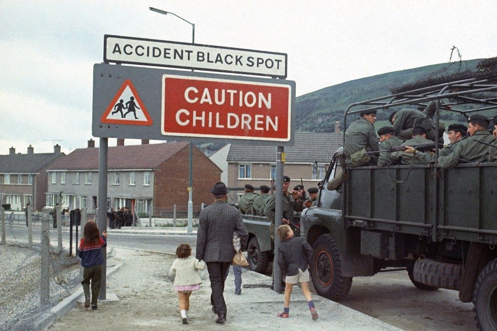 Local children look at British troops who have been sent to form a buffer during religious disputes in Northern Ireland in September 1969. (AP Photo/Royle) Ref #: PA.11410107
